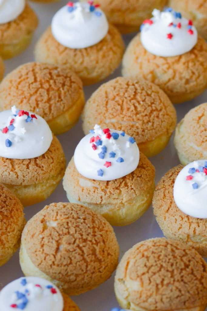 baked cream puffs with craquelin, topped with frosting and sprinkles