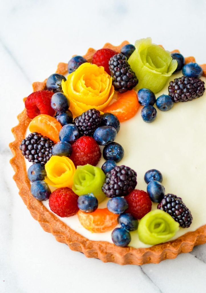 pate sucree tart filled with panna cotta topped with fresh fruit