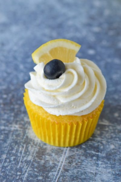 lemon buttercream on cupcake with blueberry and lemon on top
