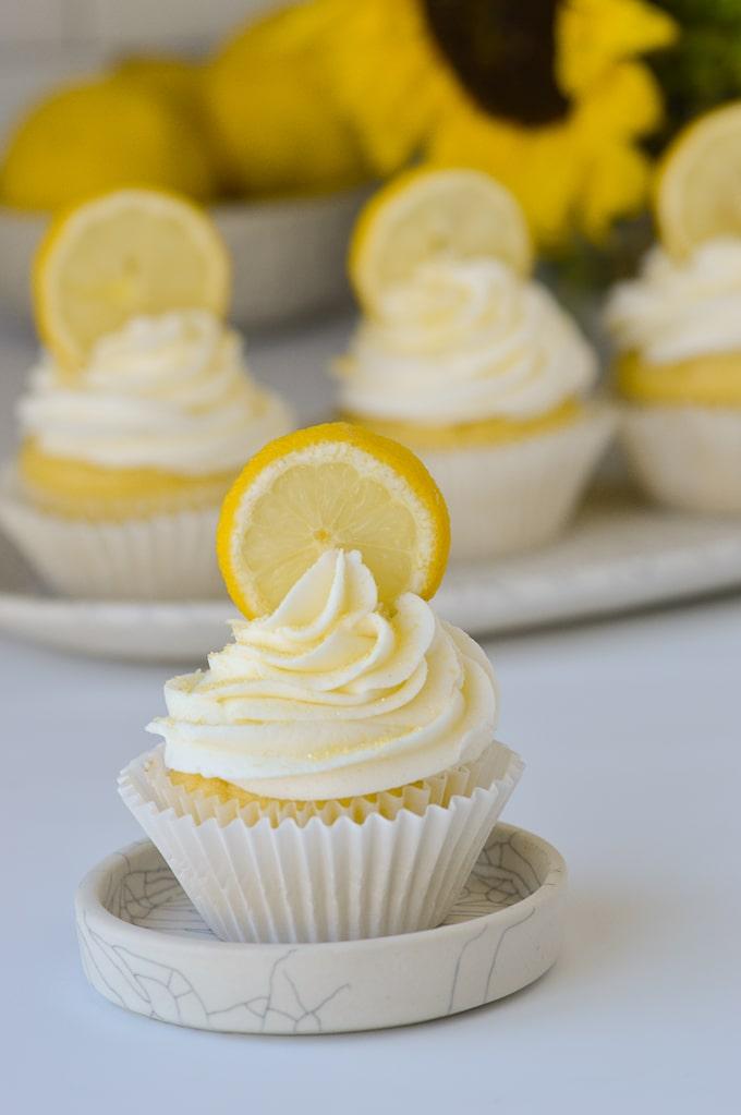cupcake with lemon buttercream yellow sprinkles and lemon slice