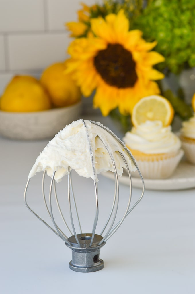 lemon buttercream on mixer whisk with cupcakes in background