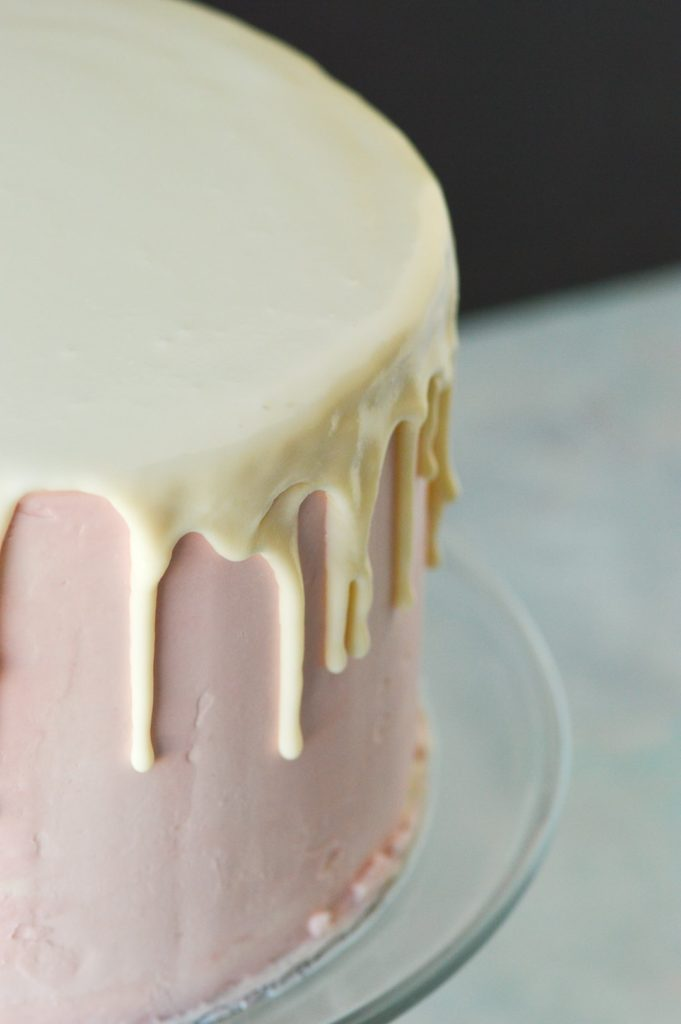 white chocolate ganache drip cake on pink buttercream frosting cake