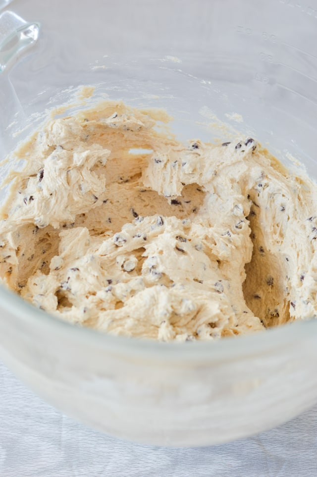 cookie dough frosting in bowl mixed with chocolate chips