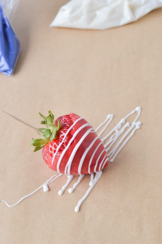 red chocolate covered strawberry with white drizzle