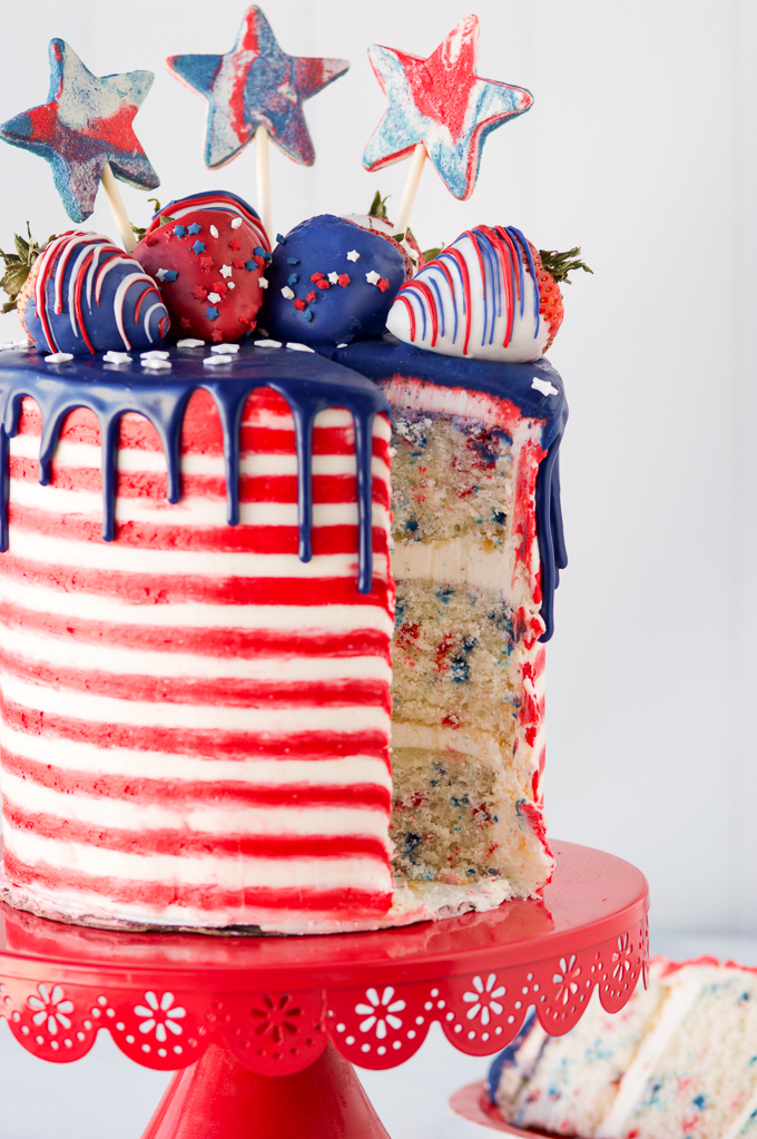 4th of july cake on red cake stand with cake slice