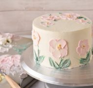 pink flowers painted in buttercream on cake on turntable
