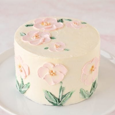 pink flowers painted in buttercream on cake