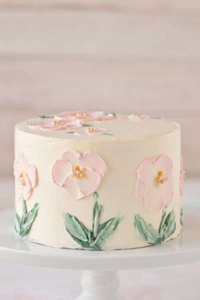 pink flowers painted in buttercream on cake up close on white cake stand