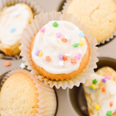 yellow cupcakes with frosting and sprinkles in cupcake holder