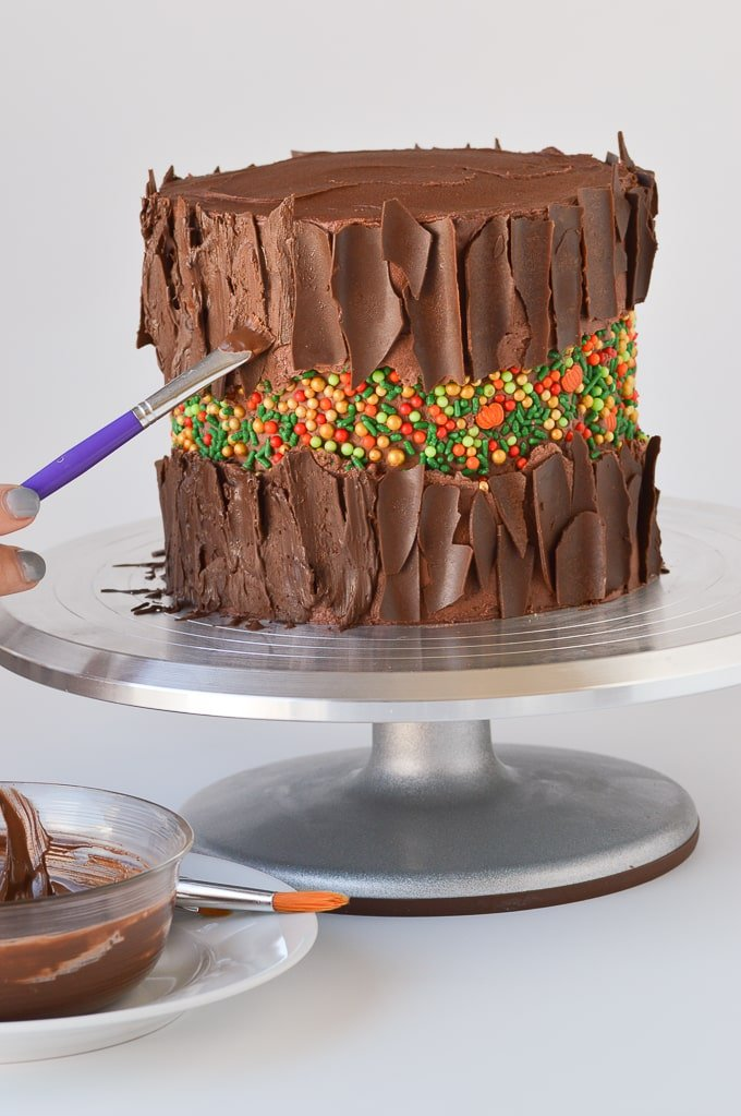 painting chocolate onto a cake to look like bark