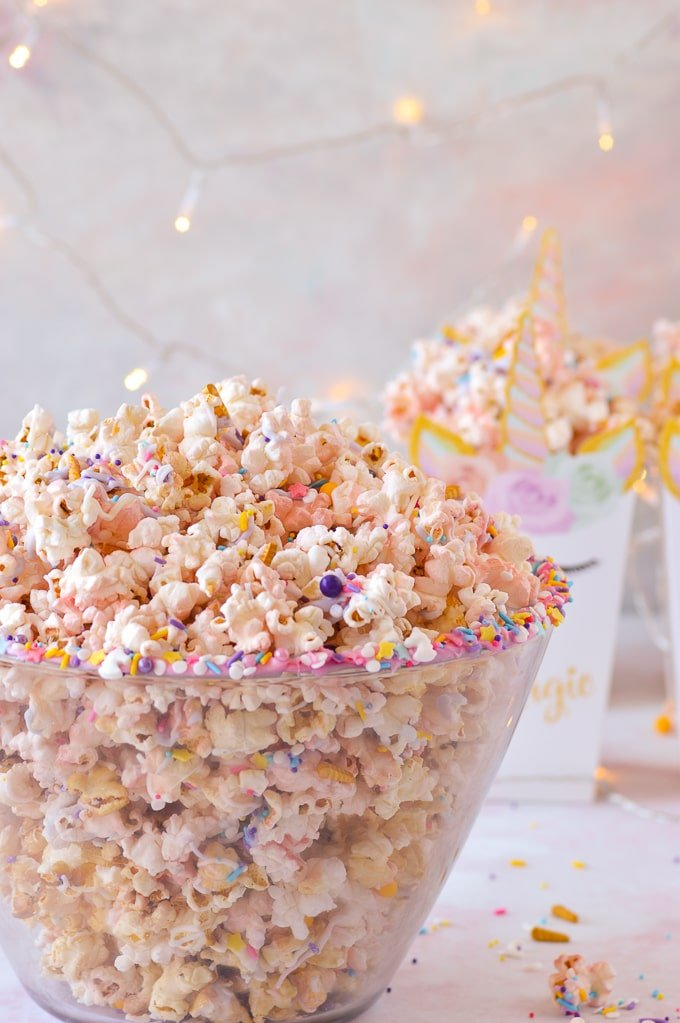 unicorn popcorn in bowl with boxes of unicorn popcorn