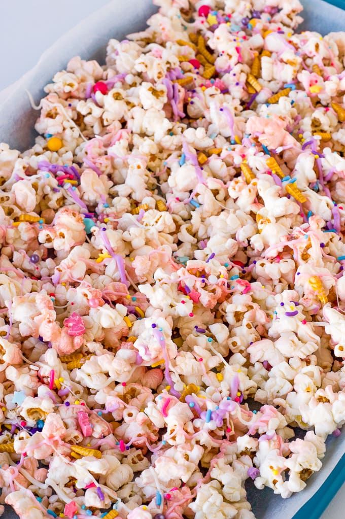 popcorn covered in melted pink and purple melted chocolate and sprinkles