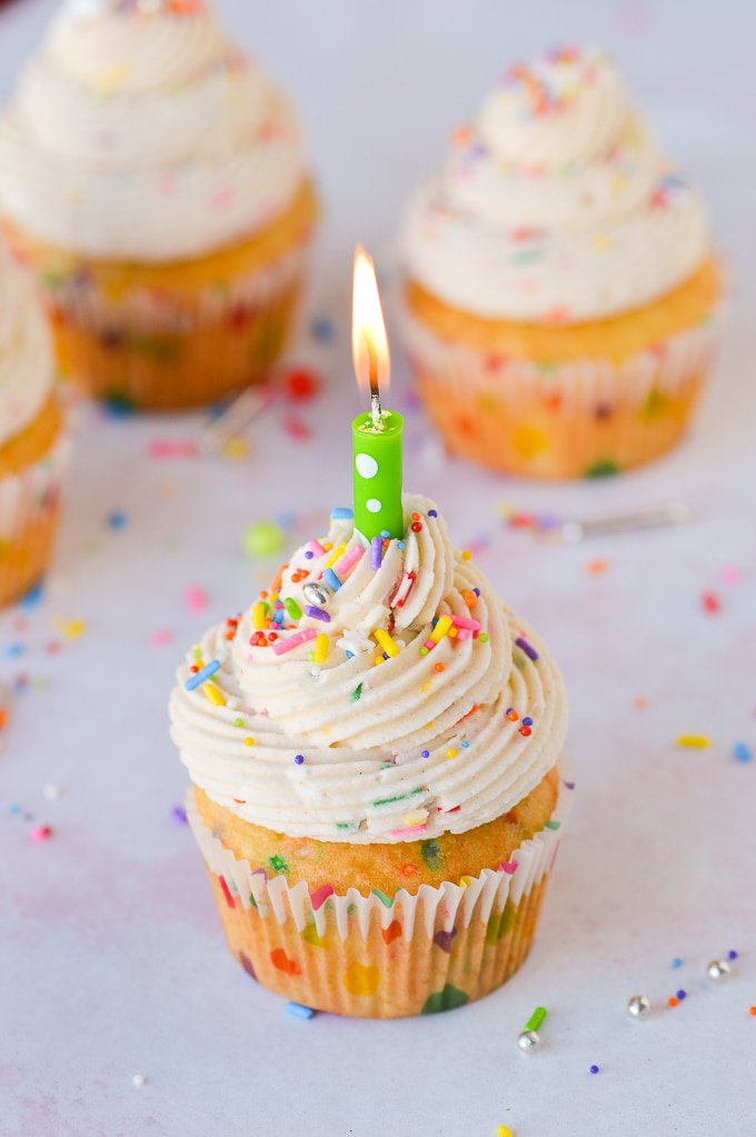 cake batter frosting on cupcake with sprinkles and lit candle