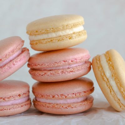 Pink and White Macarons stacked on parchment