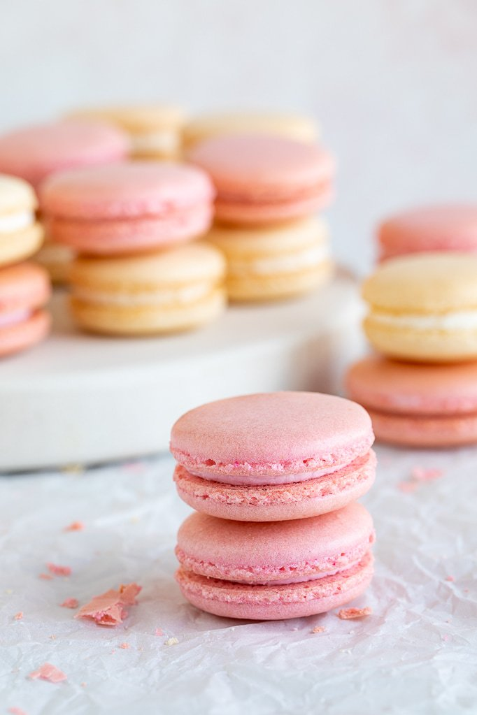 close up of pink macarons with white and pink macarons in background